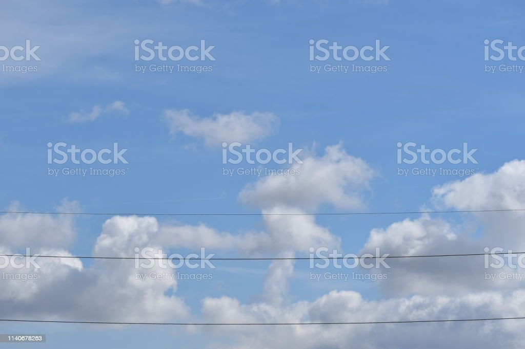 Blue Sky with Fluffy Clouds and Phone Lines stock photo