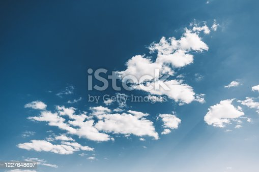 istock Blue sky with lush white clouds in the sun. 1227648697