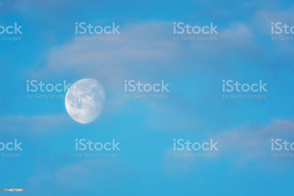 Blue sky with moon in the clouds. Can be used as background