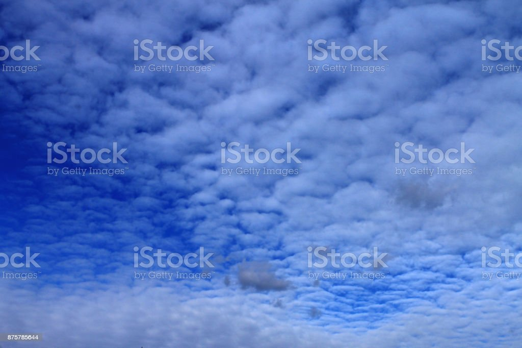Blue sky with small white and gray clouds stock photo