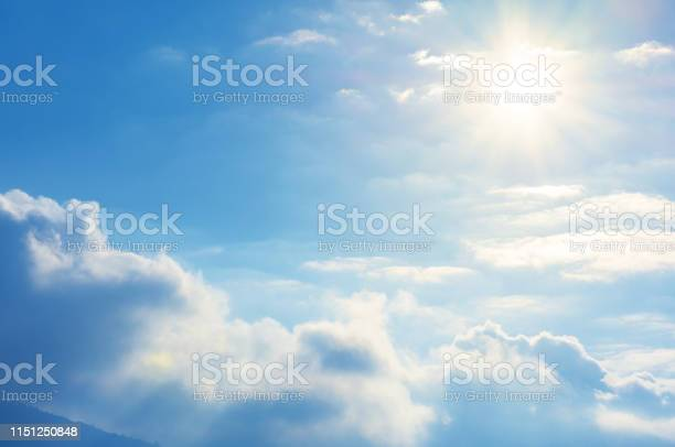 Photo of blue sky with sun and clouds