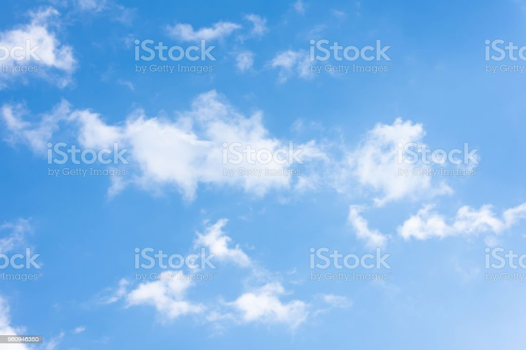 Blue sky with torn white formless clouds. stock photo