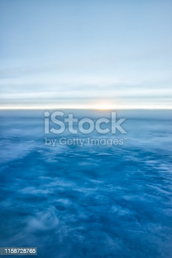 istock Blue sky with view from airplane window high angle from plane and sun setting above ocean horizon blurry background 1158728765