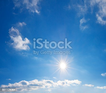 istock blue sky with white clouds and sun 931126064