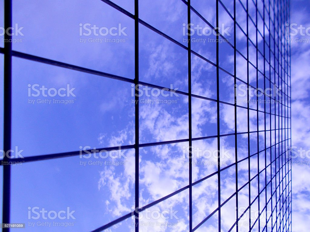 Blue sky with white clouds behind wire fence D stock photo