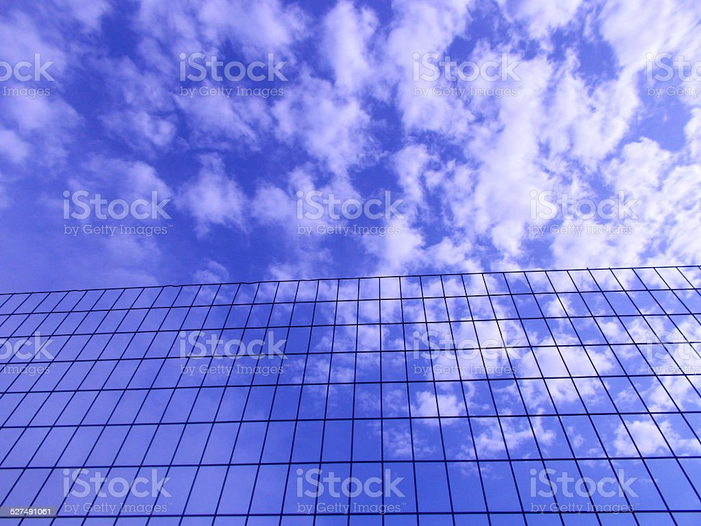 Blue sky with white clouds behind wire fence E stock photo