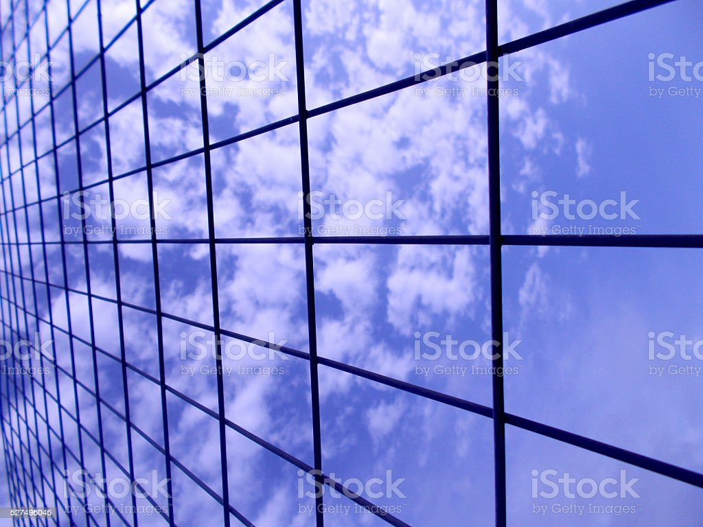 Blue sky with white clouds behind wire fence F stock photo