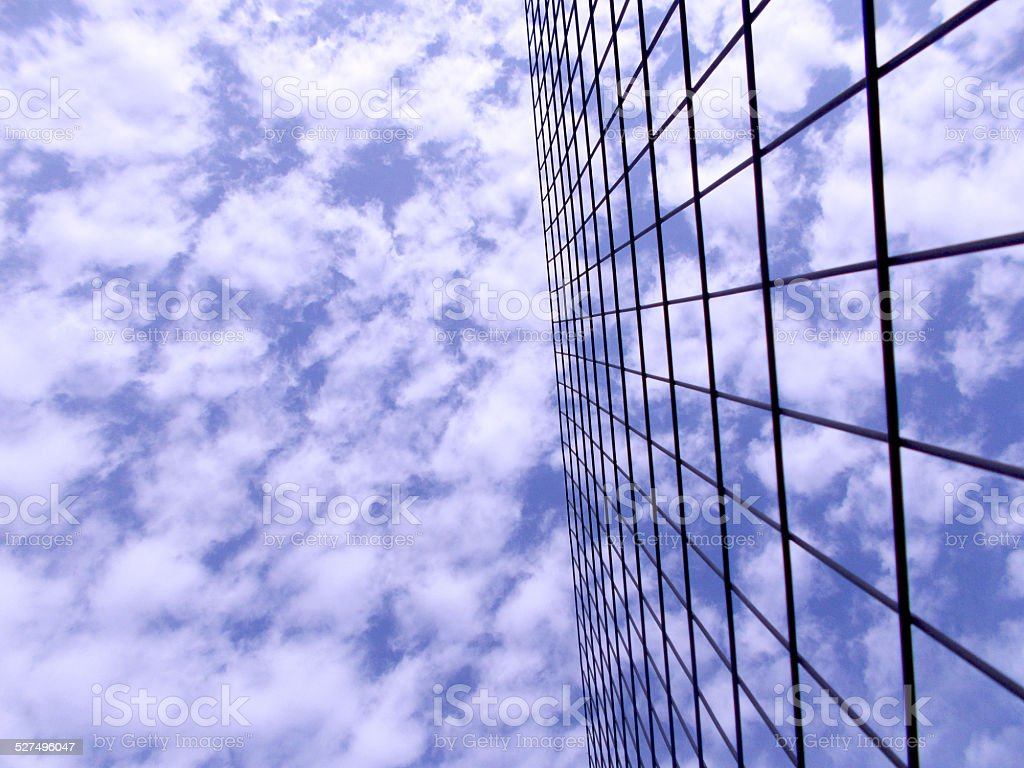 Blue sky with white clouds behind wire fence G stock photo