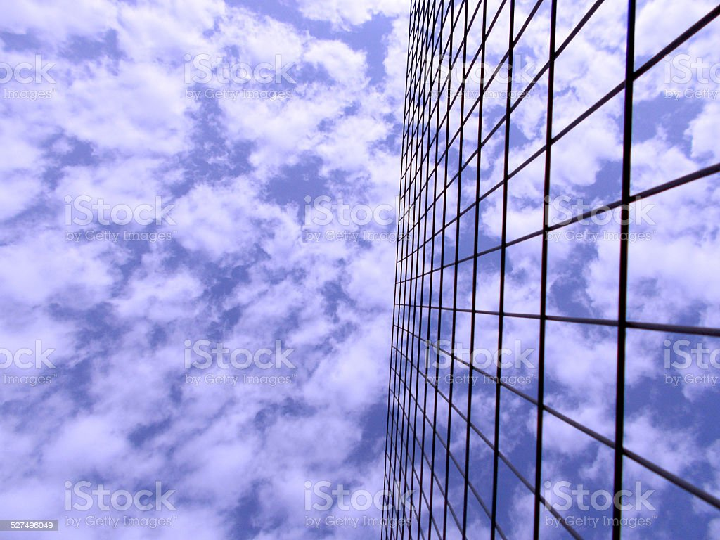 Blue sky with white clouds behind wire fence H stock photo