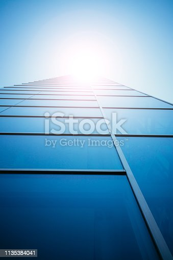 istock Blue skyscraper out of glass, sunbeam 1135384041
