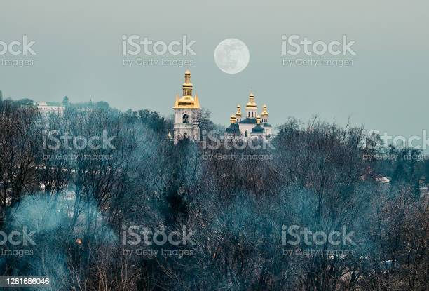 Photo of Blue smoke envelops trees without leaves. In the distance you can see the temple of God. Golden and green domes with church crosses. Cloudy autumn day. The moon hung over the grove.