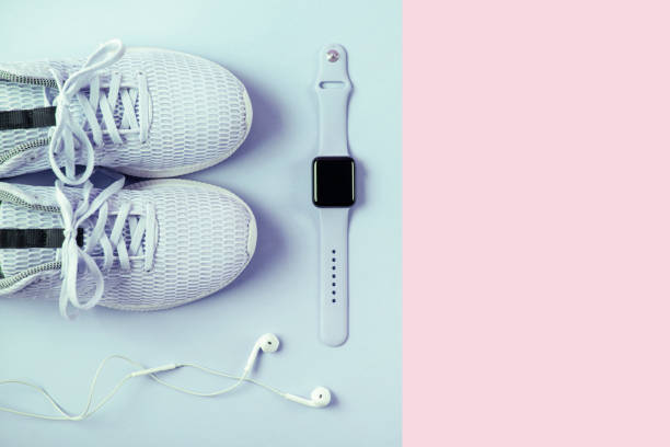 Blue sneakers, headphones and watcheson pink background. stock photo