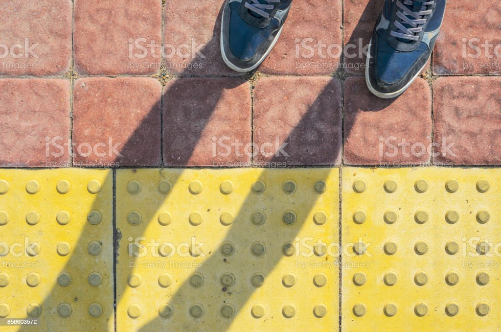 Zapatillas azul en las losas de pavimento táctil amarillo - Foto de stock de Acera libre de derechos