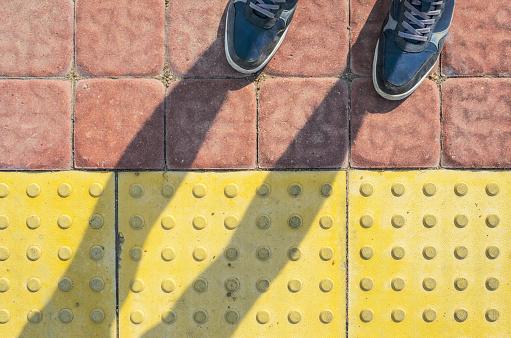 Zapatillas Azul En Las Losas De Pavimento Táctil Amarillo Foto de stock y más banco de imágenes de Acera