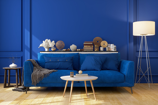 Blue Sofa In Front Of The Blue Wall With Decorative Objects And An Electric Lamp