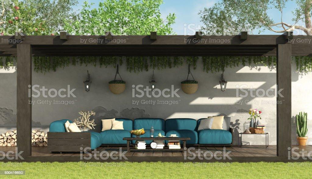 Blue sofa under a wooden pergola stock photo