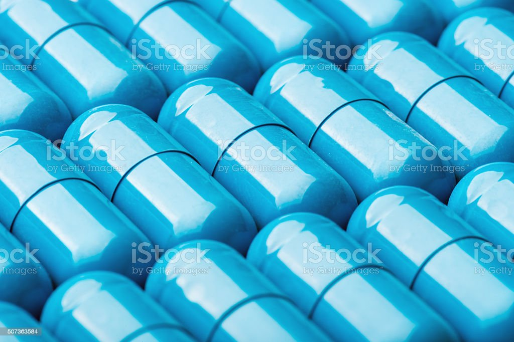 Blue softgel capsules with vitamins and minerals as background. stock photo