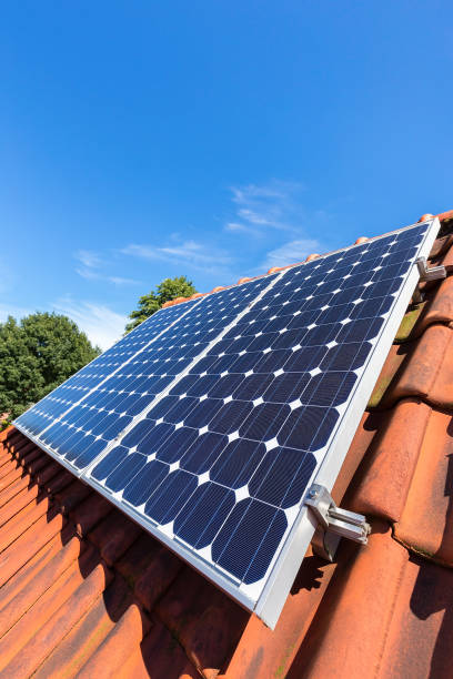 Blue solar panels  in a row on roof of house stock photo