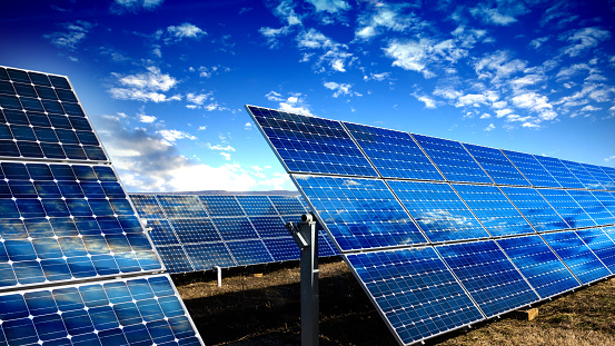 Photo voltaic solar panels and blue sky with clouds