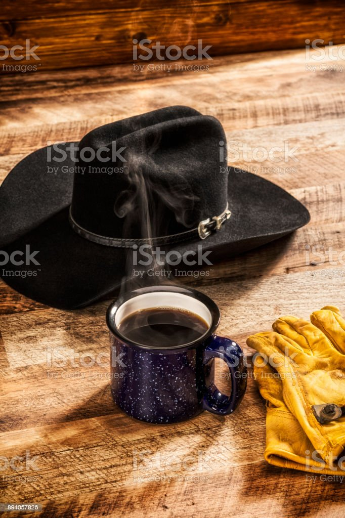c57376efbc4cc Blue speckled cup of steamy hot coffee with Cowboy hat and work gloves -  Stock image .