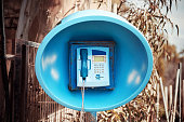 Blue spherical retro telephone booth in an outdoor rural area