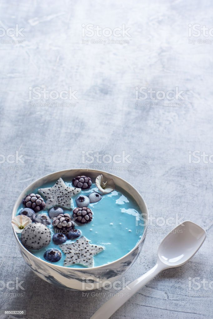 Blue Spirulina and Berry Smoothie Bowl with Fresh Fruit and Spoon stock photo