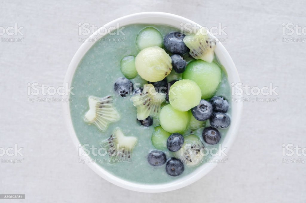 Blue spirulina smoothie bowl with melon, kiwi fruit and blueberries stock photo