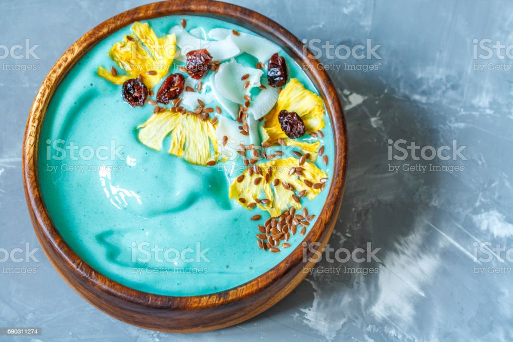 Blue spirulina smoothie bowl with pineapple and coconut. stock photo