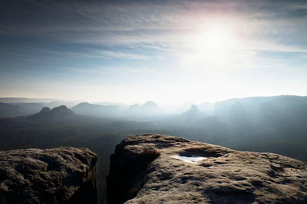 Blue spring daybreak. Sandstone cliff above deep misty valley stock photo