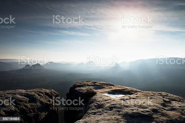 Photo of Blue spring daybreak. Sandstone cliff above deep misty valley