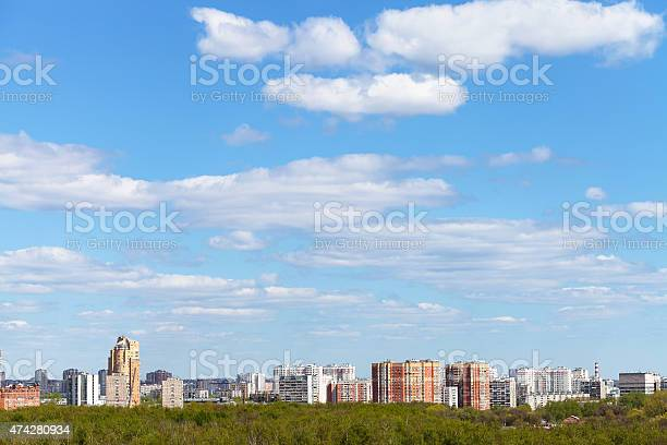 Photo of blue spring sky over city and green woods