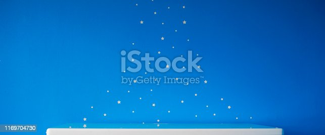 1151171813 istock photo blue starry wall and empty white table top 1169704730