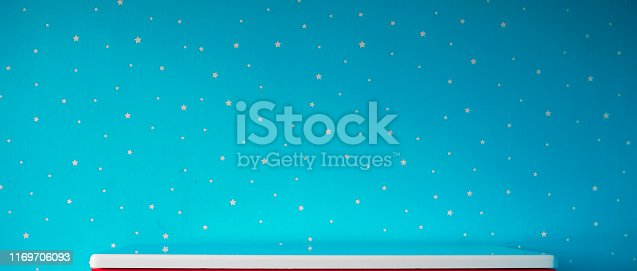1151171813 istock photo blue starry wall and empty white table top 1169706093