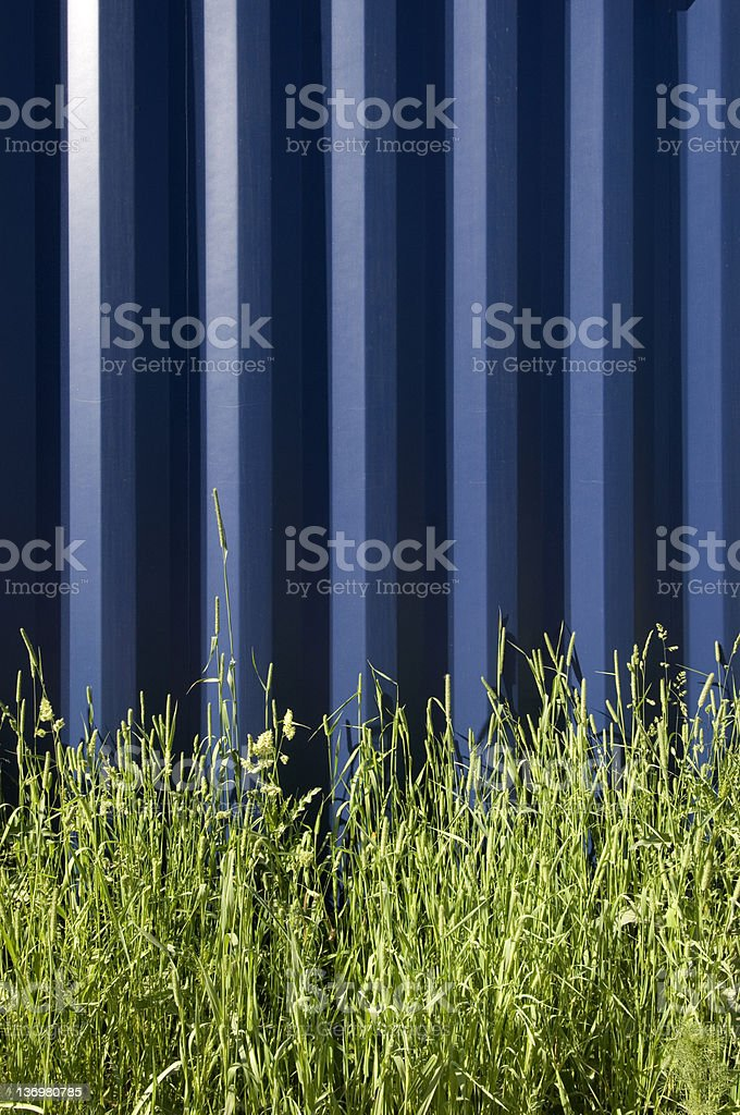 Blue steel wall with green grass royalty-free stock photo