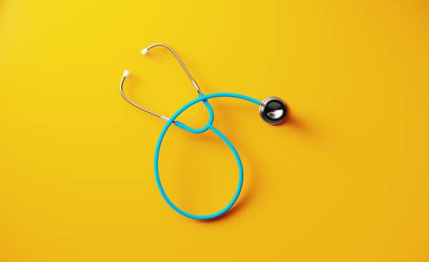 Blue Stethoscope On Yellow Background stock photo