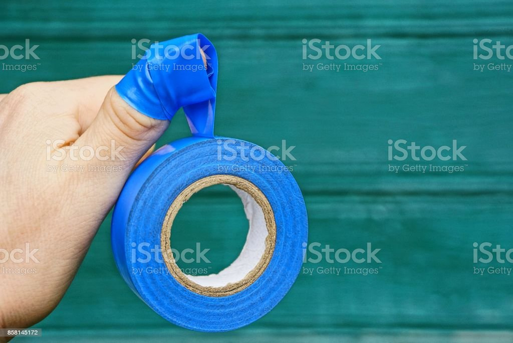 blue sticky tape on fingers of a hand on a green background stock photo