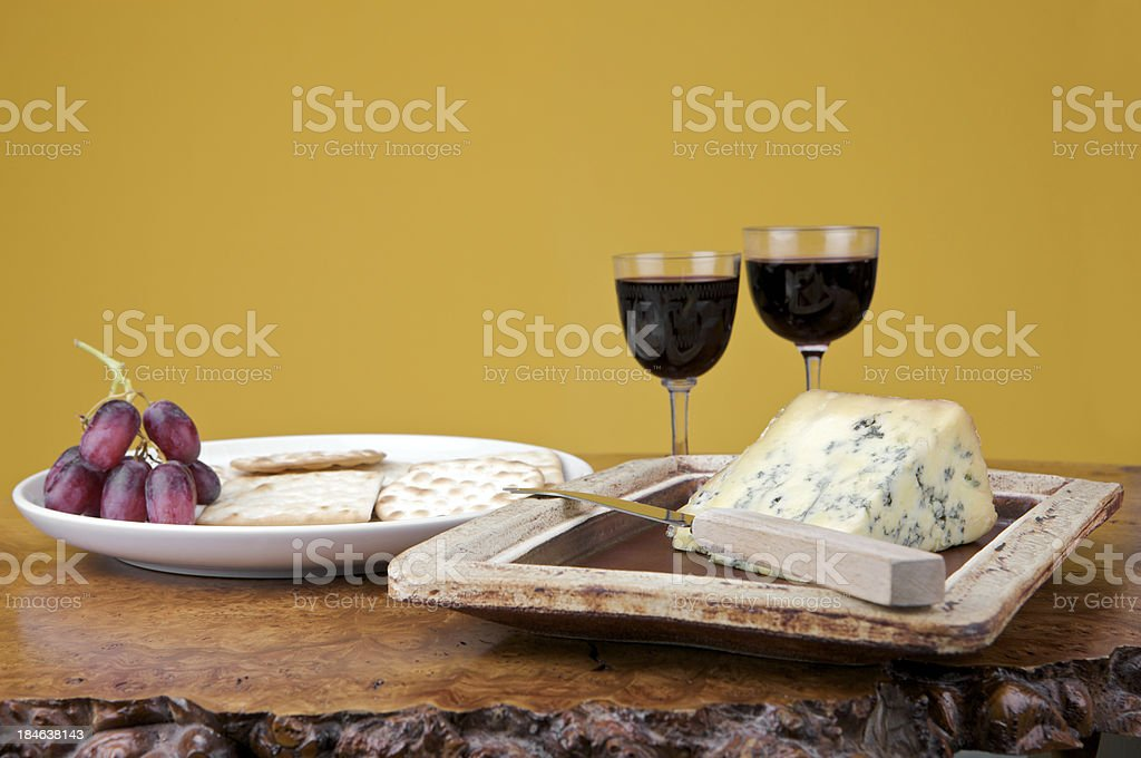 Blue stilton cheese with biscuits, grapes and glasses of port royalty-free stock photo