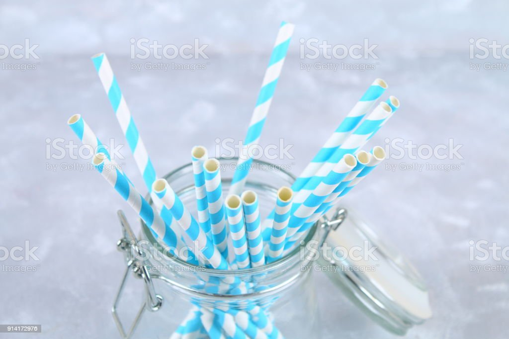 Blue striped paper disposable tubes in a jar on a gray background. stock photo