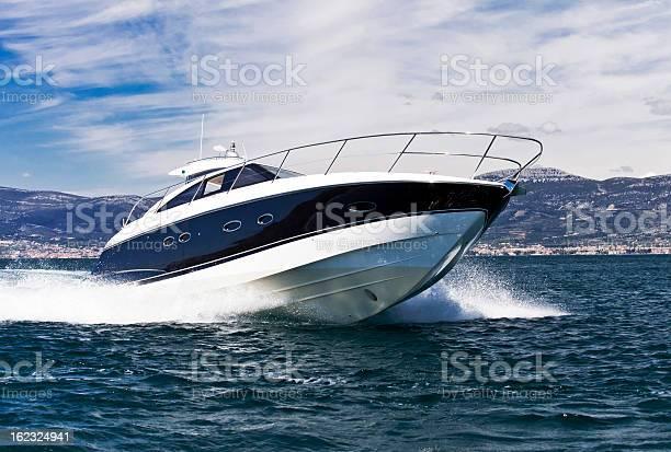 Photo of A blue striped white yacht speeding across the sea