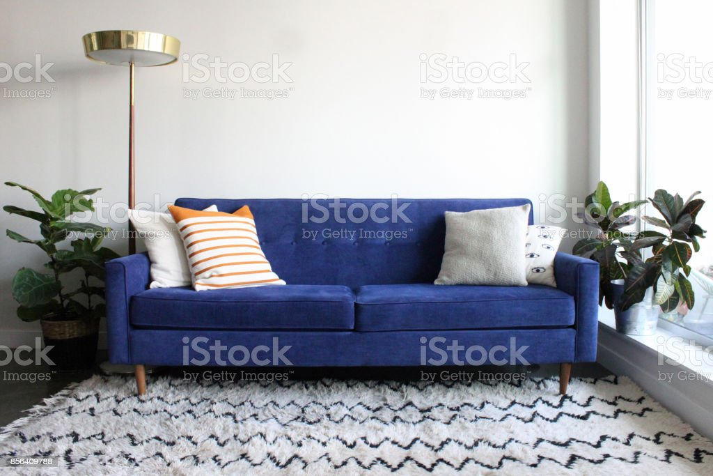 Blue Suede Mid Century Modern Couch in Minimalist Apartment Setting stock photo