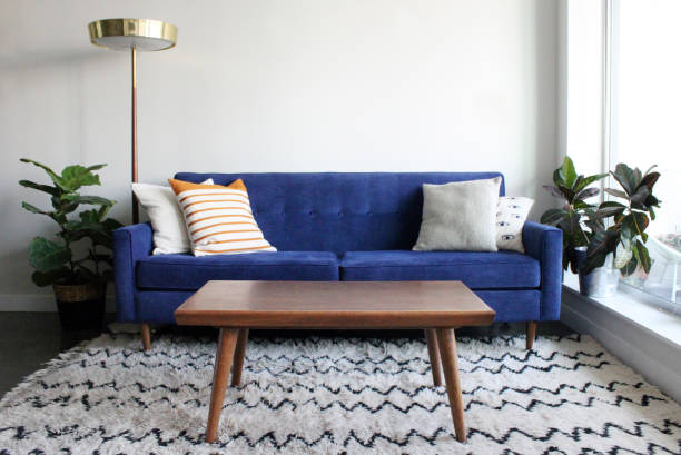 blue suede mid century modern couch in minimalist apartment setting - coffee table imagens e fotografias de stock