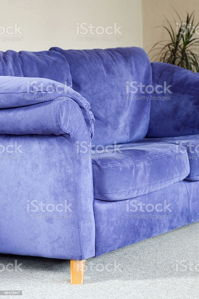 Blue suede sofa on oatmeal floor royalty-free stock photo