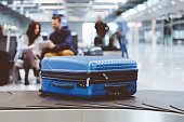 Blue suitcase on conveyor at baggage claim line terminal of the international airport. People in the background.