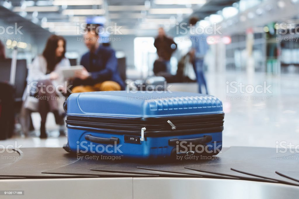 Blauen Koffer auf Förderband am Flughafen mit Menschen im Hintergrund – Foto