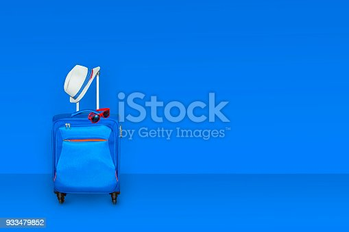 istock Blue suitcase with a summer hat and fashionable  sunglasses on light blue background, a summer vacation travel concept, free space with a place for copying, 3d rendering 933479852