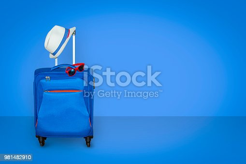 istock Blue suitcase with a summer hat and fashionable sunglasses on light blue background, a summer vacation travel concept, free space with a place for copying 981482910