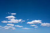 Blue summer sky with cumulus clouds in white as a background
