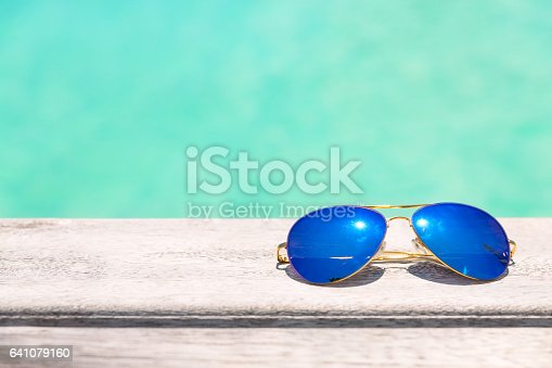 Blue Sunglasses on a wooden deck, summer holiday concept