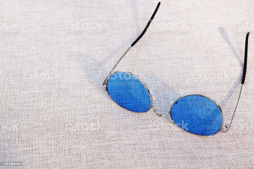 Blue sunglasses on a woven cloth stock photo