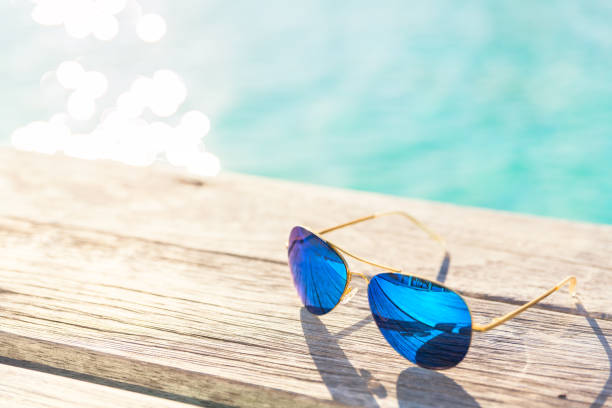 Blue Sunglasses on wooden decking by seaside Blue Sunglasses on wooden decking by seaside poolside stock pictures, royalty-free photos & images